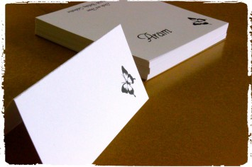 Black butterfly place cards on classic white paper.