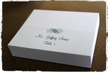 Classic swirls place card on folded classic white paper in marine ink.